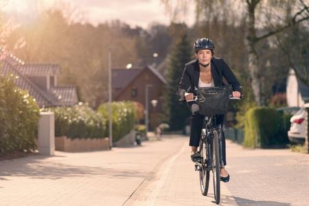 Jonge zakenvrouw rijden om te werken op een fiets langs een residentiële straat in haar stijlvolle slappe pak en helm op een milieuvriendelijke wijze van vervoer