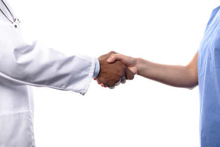 Close Up of Unidentifiable Medical Professionals Shaking Hands, One Wearing White Lab Coat and the Other Wearing Blue Scrubs, with White Background Stockfoto