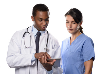 male doctor: Two medical colleagues consulting a tablet-pc looking up patient records and charts with a handsome young African doctor in a white lab coat and attractive woman nurse or surgeon in scrubs, on white