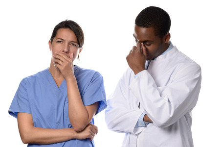 overpowered: Tired worried doctor and nurse or surgeon in scrubs standing with their hands to their faces and serious expressions after a long operation or procedure as they ponder the outcome, isolated on white Stock Photo