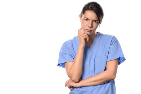 Moedeloos jonge vrouwelijke arts of verpleegkundige dragen blauwe chirurgische scrubs staren somber op de vloer met een peinzende uitdrukking, geïsoleerd op wit