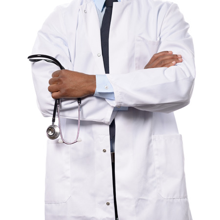 the cardiologist: African doctor, surgeon, cardiologist or nurse in a white lab coat, standing with folded arms holding a stethoscope in her hands, torso view isolated on white
