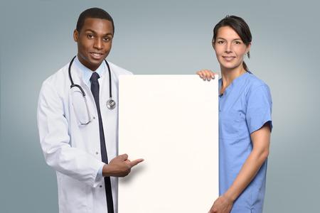 Multiethnischen Ärzteteam eines afrikanischen Arzt in einem Laborkittel und Stethoskop und eine Krankenschwester in Scrubs hält ein leeres weißes Schild mit copyspce für Ihren Text auf sie zeigen mit glücklichen freundlichen Lächeln
