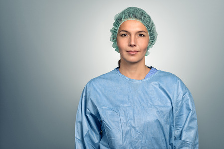 nurse cap: Attractive middle-aged female doctor or nurse in scrubs and a sterility cap looking directly at the camera over a grey background, head and shoulders portrait