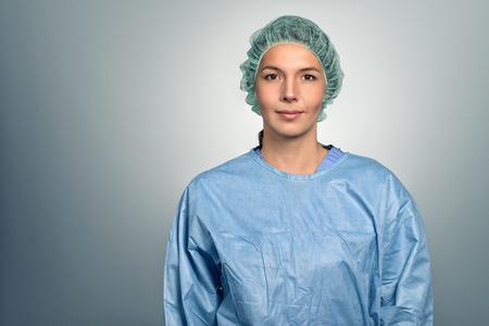 enfermera con cofia: Doctor atractivo de mediana edad femenina o enfermera en matorrales y una tapa de la esterilidad que mira directamente a la c�mara sobre un fondo gris, la cabeza y los hombros retrato