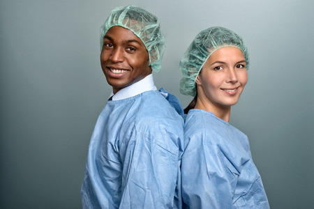 Handsome young African doctor or male nurse in scrubs and a sterility cap looking directly at the camera over a grey background, head and shoulders portrait