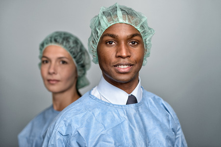 sterility: Confident Male and Female Medical Professionals Smiling at the Camera, Isolated on White Background.