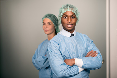 sterility: Confident Male and Female Medical Professionals Smiling at the Camera wearing blue scrubs and sterility cap