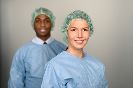 hospital gown: Confident Male and Female Medical Professionals Smiling at the Camera wearing blue scrubs and sterility cap