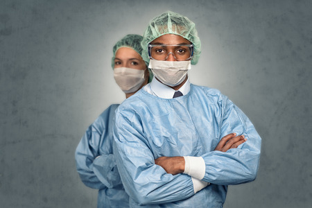 Confident Male and Female Medical Professionals Smiling at the Camera wearing blue scrubs and sterility cap