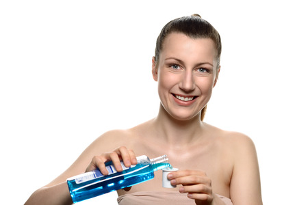 mouthwash: Close up Smiling Young Woman Pouring a Bottle of Mouthwash into a Cap While Looking at the Camera, Isolated on White Background.