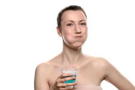 femme blonde: Femme heureuse saine rin�age et de se gargariser en utilisant un rince-bouche � partir d'un verre, au cours de la routine quotidienne de l'hygi�ne buccale, portrait, les �paules nues, avec copie espace, isol� sur blanc Banque d'images