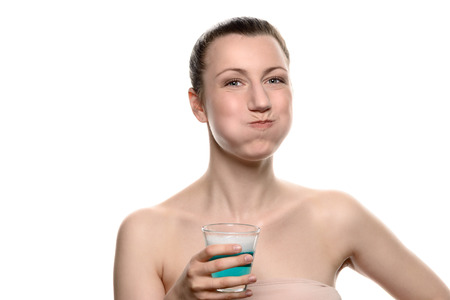 enjuague bucal: Mujer feliz saludable enjuagar y hacer gárgaras durante el uso de enjuague bucal de un vaso, durante la rutina de higiene oral diaria, retrato con los hombros desnudos, con copia espacio, aislado en blanco