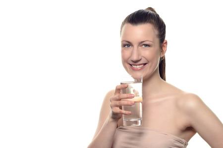 elasticity: Mujer bonita joven que desgasta Tube Tops, sostiene un vidrio de un agua potable mientras sonriendo a la cámara, aislado en blanco