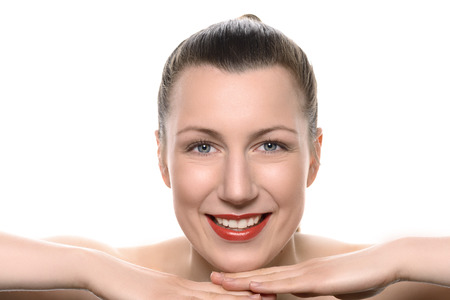 vivacious: Pretty healthy woman wearing red lipstick resting her chin on her hands looking at the camera with a vivacious friendly smile full of vitality in a wellness and beauty concept on white with copy space