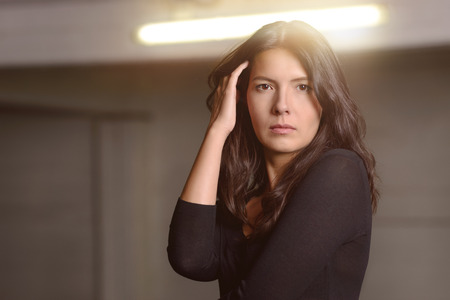 unemotional: Serious attractive woman staring at the camera with an unemotional enigmatic expression and her hand to her hair indoors under a fluorescent light