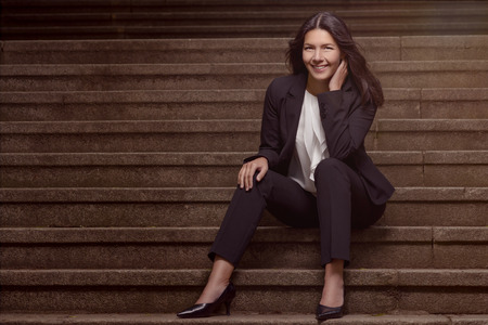 slack: Smiling stylish woman in a dark slack suit sitting on a flight of concrete steps with her hand raised to her cheek looking at the camera with a lovely warm friendly smile, with copyspace Stock Photo