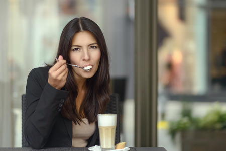 energising: Woman sitting in a coffee house or cafeteria savoring a tasty cup of cappuccino coffee sipping the frothy foam off a spoon while looking at the camera