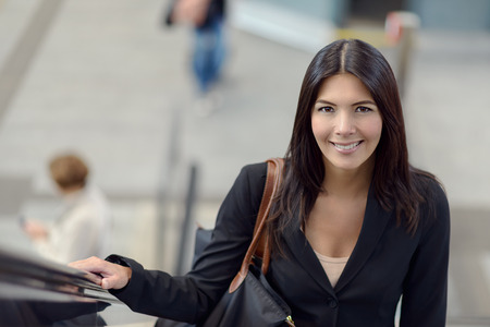 public space: Smiling brunette is riding the escalator in public space