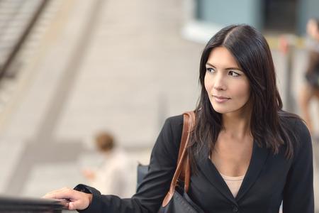hand rails: Attractive brunette businesswoman riding the escalator in public space Stock Photo