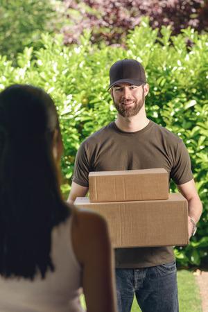 cartero: Mujer abrir la puerta a un repartidor barbudo atractivo que lleva dos cajas de cartón para la entrega, ver por encima del hombro desde atrás