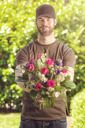 three quarter length: Three quarter length front view of smiling bearded 20s man wearing brown baseball cap, brown t-shirt and jeans holding bunch of flowers.