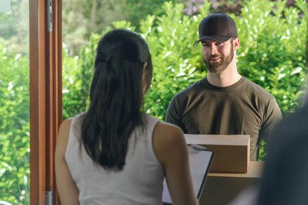 delivery box: Woman accepting a delivery of two cardboard boxes with an order or gift signing the clipboard for the friendly smiling deliveryman on the doorstep Stock Photo