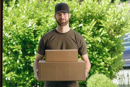 deliveryman: Handsome delivery man or courier with two cardboard boxes in his arms standing waiting to make the door to door delivery at a private house