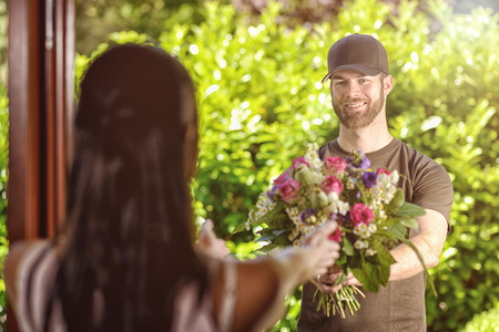delivers: Smiling bearded 20s man wearing brown cap and brown t-shirt delivers flowers to door of young brunette female. Over the shoulder rear view of brunette.