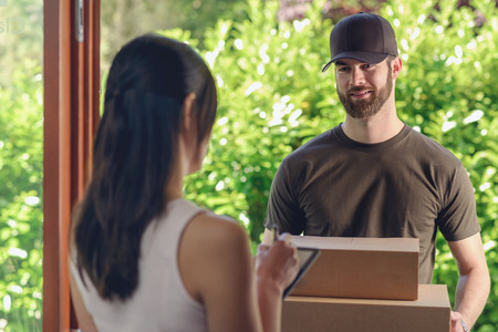 accepting: Woman accepting a delivery of two cardboard boxes with an order or gift signing the digital clipboard for the friendly smiling deliveryman on the doorstep