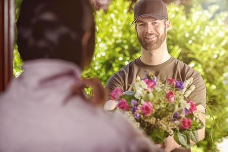 갈색 모자와 갈색 셔츠를 입고 수염을 기른 20 대 남자 웃는 젊은 갈색 머리 여성의 문에 꽃을 제공합니다. 갈색 머리의 어깨 리어 뷰 위에. 스톡 콘텐츠