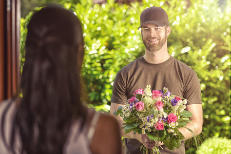 Smiling bearded 20s man wearing brown cap and brown t-shirt delivers flowers to door of young brunette female. Over the shoulder rear view of brunette.