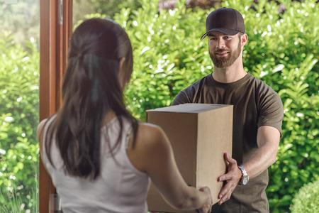 cartero: Deliveryman o cartero haciendo una entrega puerta a puerta de entrega a través de una gran caja de cartón a un ama de casa, vista desde atrás por encima del hombro del hombre