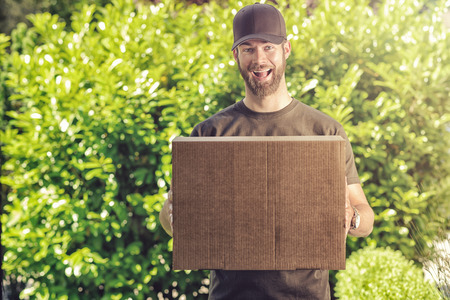 delivers: Cute bearded guy in a peaked cap with a happy exuberant grin making a delivery of a large brown cardboard box carrying it in his hands against a garden backdrop of fresh green leaves