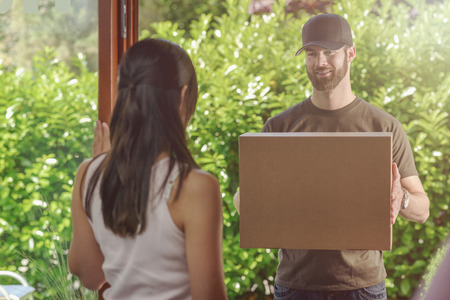 answering: Woman answering the door to an attractive bearded deliveryman carrying two cardboard cartons for delivery, view over her shoulder from behind