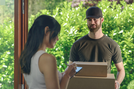 mail delivery: Woman accepting a delivery of two cardboard boxes with an order or gift signing the digital clipboard for the friendly smiling deliveryman on the doorstep