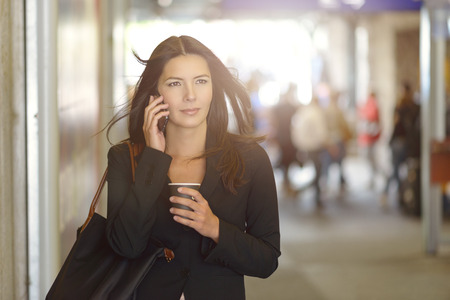 Aantrekkelijke jonge zakenvrouw bellen op mobiele telefoon, Wandelen in het winkelcentrum terwijl u een kopje koffie. Stockfoto