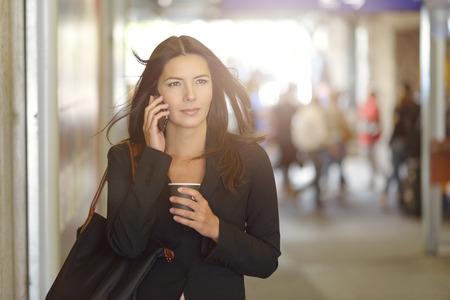 llamando: Empresaria joven atractiva hablando por teléfono móvil, Corta En el interior del centro comercial, mientras sostiene una taza de café.
