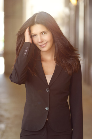 lapels: Portrait of Professional Brunette Woman Wearing Suit Jacket, Smiling at Camera Outdoors with Hand in Hair Stock Photo