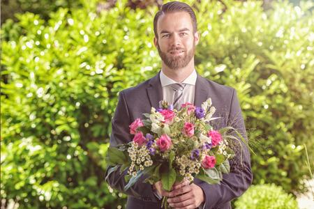 flores de cumpleaños: Joven barbudo hermoso en un juego que lleva un ramo de flores frescas, posiblemente un pretendiente o novio llamar en una fecha, día de San Valentín, un aniversario o un cumpleaños, en un contexto de hojas verdes