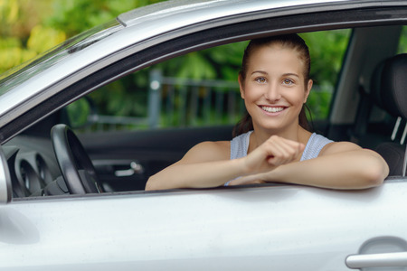 female driver: Pretty Young Woman Sitting Inside the Car, Smiling at the Camera While Leaning on the Open Window Stock Photo