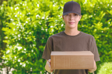 order delivery: Attractive delivery woman or courier with a cardboard box in her arms standing waiting to make the delivery at a private house Stock Photo