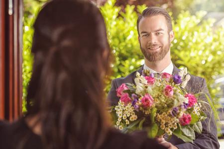 compleanno: Bel ragazzo barbuto che d� un mazzo di fiori freschi alla sua fidanzata con felice espressione del viso.