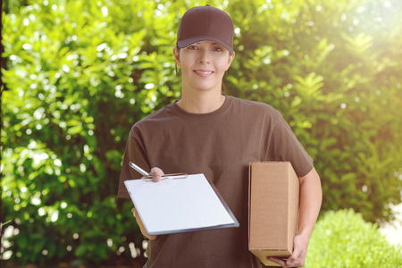 mail order: Smiling attractive female courier in a cap delivering a parcel to the door of a house holding out a clipboard for signature to acknowledge receipt, against a background of fresh garden leaves