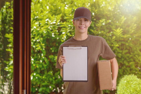 acknowledge: Smiling attractive female courier in a cap delivering a parcel to the door of a house holding out a clipboard for signature to acknowledge receipt, against a background of fresh garden leaves