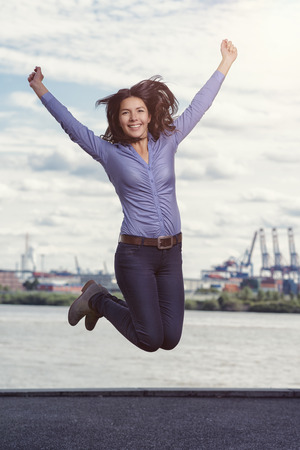 glee: Young woman leaping and cheering for joy with her arms raised and a triumphant smile of glee against a waterway and distant city backdrop