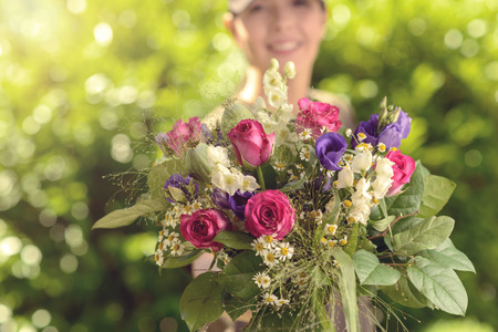 bunch of flowers: Woman at the Garden Offering Bouquet of Assorted Fresh Flowers at the Camera in Close up.
