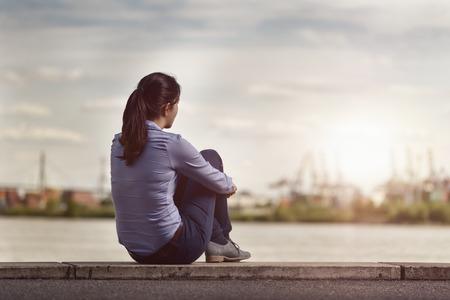 Vue arrière d'un Réfléchi jeune femme face à la rivière alors qu'il était assis sur un long banc en béton et serrant ses jambes