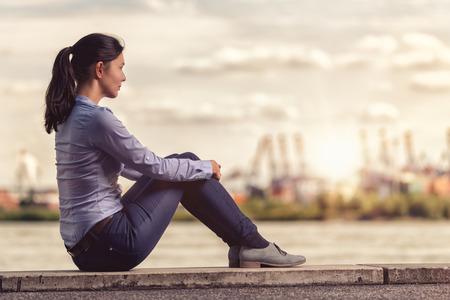 mujeres de espalda: Vista trasera de una mujer joven pensativo frente al río, mientras que sentado en un banco de hormigón Largo y abrazando sus piernas