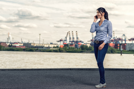 Attractive brunette happy woman wearing casual outfit as blue skinny jeans and shirt, while talking on mobile phone and walking on shore along the river in a cloudy day